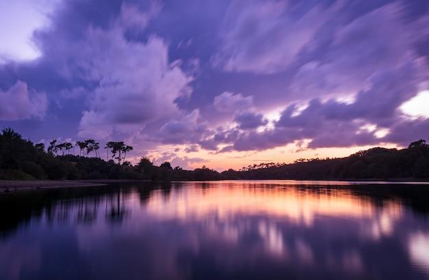 Cenário de tirar o fôlego com as nuvens do pôr do sol refletindo no lago jaunay, na frança