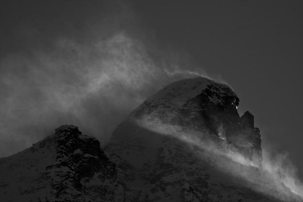 Cenário de tirar o fôlego com montanhas cobertas de neve sob um céu nublado