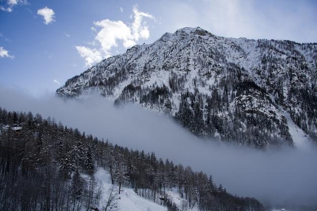 Cenário de tirar o fôlego das montanhas cobertas de neve sob um céu nublado panorâmico