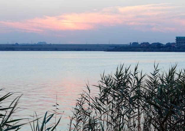 Cenário do lago à noite com juncos na frente e o reflexo do sol na superfície da água.