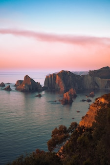 Cenário do mar com penhascos durante o pôr do sol - papel de parede perfeito