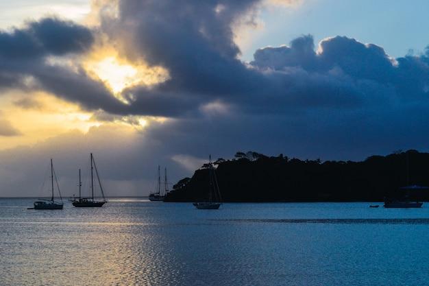 Cenário do pôr do sol com silhueta de montanha e barcos no mar