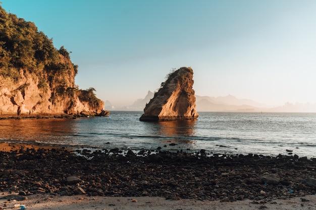 Cenário do pôr do sol com uma bela formação rochosa na praia do rio de janeiro, brasil