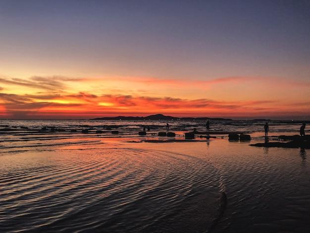 Cenário do pôr do sol com uma silhueta de pessoas na praia