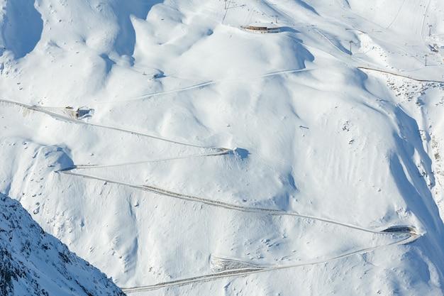 Cenário do teleférico da cabine na estrada serpentina na encosta nevada (tirol, áustria). todas as pessoas estão irreconhecíveis.