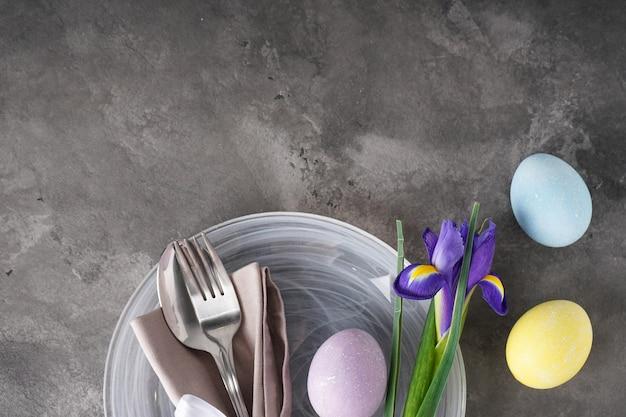 Cenário e pratos de mesa para o feriado da páscoa com ovos coloridos em cinza