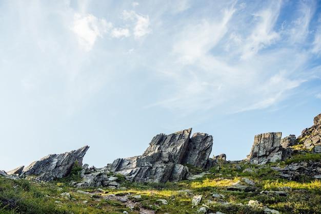 Cenário ensolarado das montanhas com pedras afiadas de forma incomum. impressionante paisagem montanhosa cênica com grandes pedras pontiagudas rachadas closeup entre grama sob o céu azul na luz solar. rochas pontiagudas com rachaduras