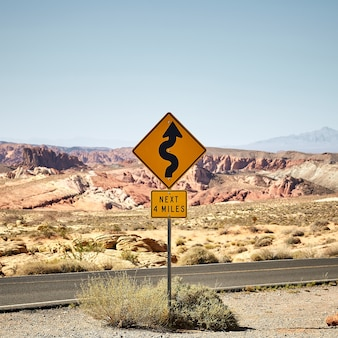 Cenário ensolarado de uma placa de sinalização de trânsito amarela no parque estadual valley of fire em nevada, eua