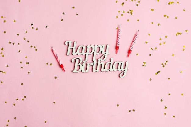 Cenário festivo de decoração de estrelas brilhantes, velas para bolo e texto feliz aniversário em um fundo rosa.