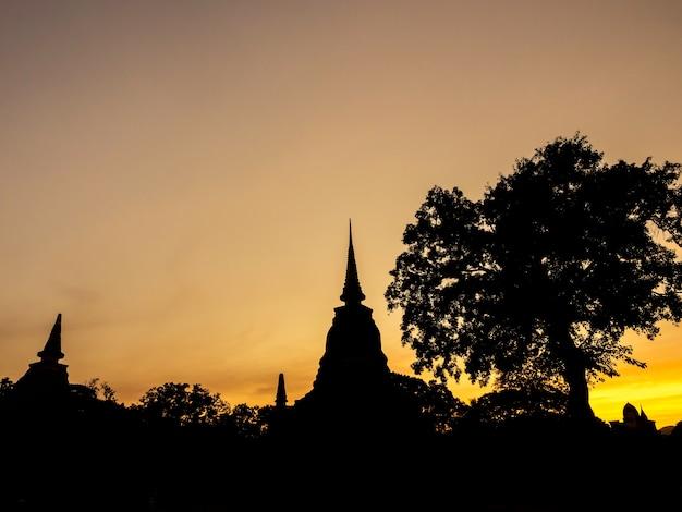 Cenário incrível da silhueta do pagode, do templo e do céu dourado do pôr do sol no parque histórico de sukhothai, um patrimônio mundial da unesco na tailândia.