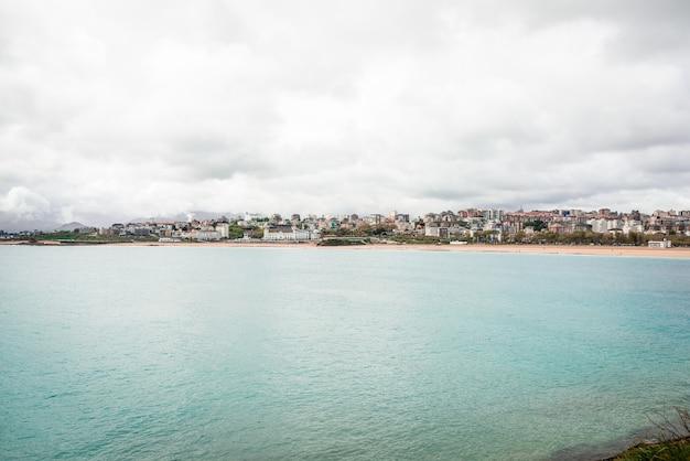 Cenário pitoresco de uma cidade costeira localizada perto de uma praia de mar ondulado e céu nublado