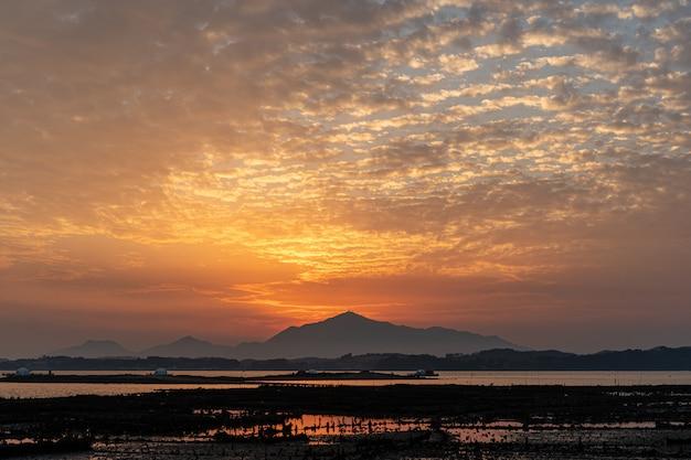 Cenário por do sol com os planos de lama e a geumo-montanha no mar do sul, coréia
