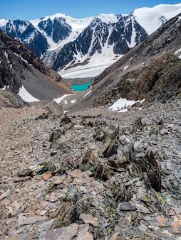 Cenário serrano com pedras afiadas de formas incomuns. impressionante paisagem montanhosa cênica com grande closeup de pedras pontiagudas rachadas entre a neve sob o céu azul na luz solar. rochas afiadas.