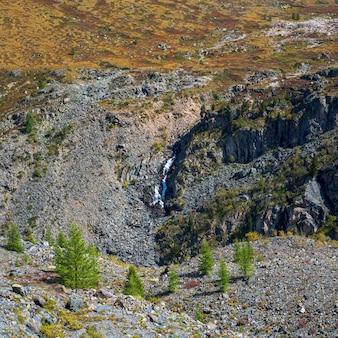 Cênica paisagem alpina com árvores no vale e grande cordilheira com cachoeira na luz do sol. paisagem colorida da natureza com belas montanhas. vista quadrada.