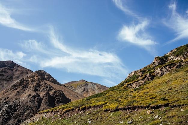 Cênica paisagem montanhosa com lindas nuvens cirros em um céu azul claro sobre rochas sob a luz do sol