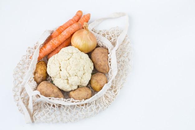 Cenoura, batata e couve-flor em um saco de corda