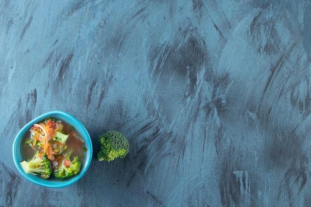 Cenoura, brócolis e tigela de canja de galinha, sobre o fundo azul.