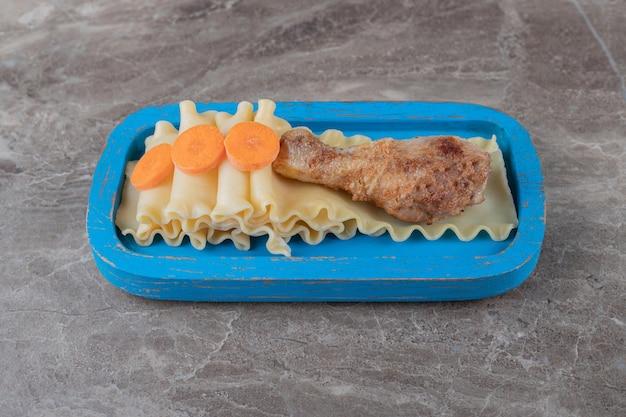 Cenoura cortada ao lado da coxa nos macarons na bandeja azul, no mármore.