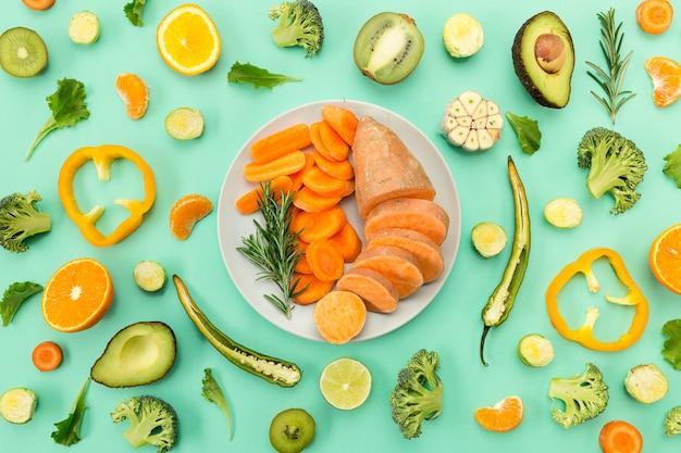 Cenoura e batata doce cercadas por fatias de vegetais