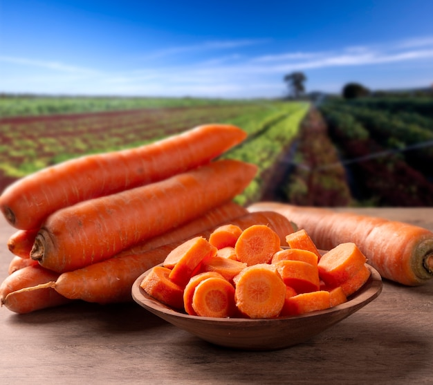 Cenoura e cenoura fatiada na mesa de madeira com fundo de plantação.