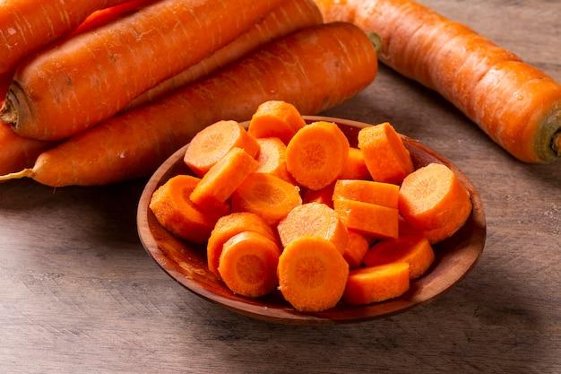 Cenoura e cenoura fatiada na mesa de madeira. foco seletivo.