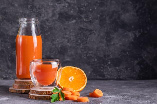 Cenoura e suco de laranja em uma garrafa e copo em porta-copos de madeira copiam o espaço