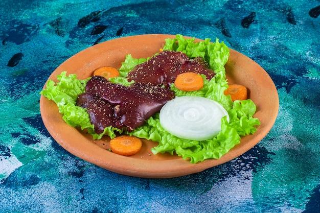 Cenoura fatiada, cebola em folhas de alface e fígado de galinha em uma tigela de barro