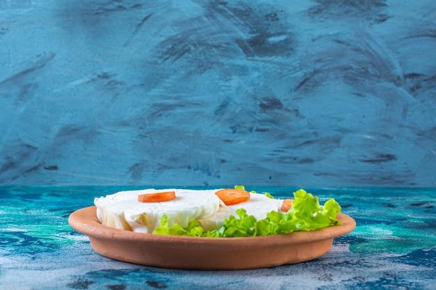 Cenoura fatiada, couve e folhas de alface em um prato