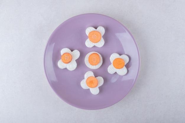 Cenoura fresca fatiada e rabanete no prato na mesa de mármore.
