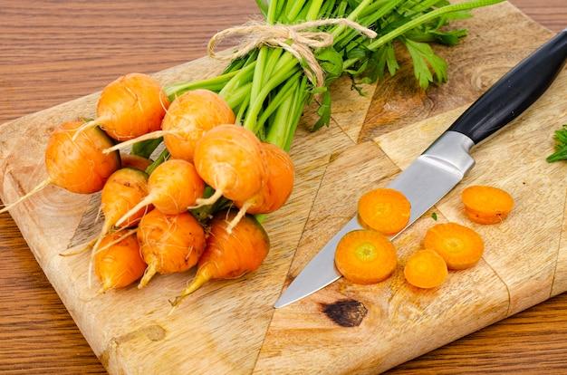 Cenoura laranja redonda na placa de madeira com faca.