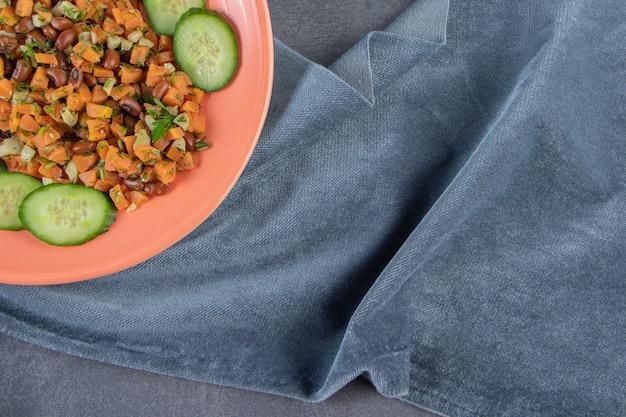 Cenoura picada, feijão e pepino em um prato na toalha ao lado de cenouras inteiras, no fundo de mármore.