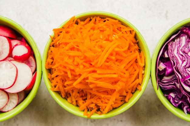 Cenoura picada fresca; repolho e rabanete em tigela verde