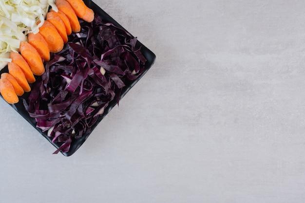 Cenoura picada, repolho vermelho e branco na placa preta. foto de alta qualidade