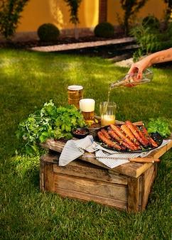 Cenouras assadas no forno na placa preta na caixa de madeira no jardim. mulher está derramando urso no copo com a mão tatuada.