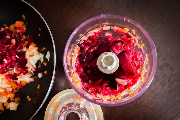Cenouras, beterrabas e cebolas são cortadas para fritar borsch em um helicóptero elétrico. sopa de cozinhar.