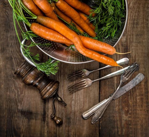 Cenouras com folhas verdes sobre fundo de madeira rústico. comida saudável. vegetal