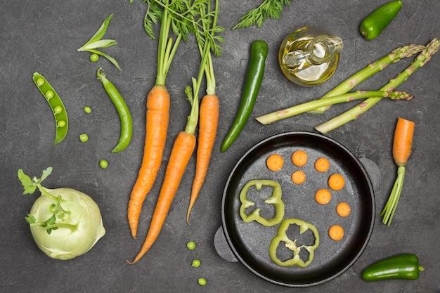 Cenouras com tops, aspargos e azeite na mesa
