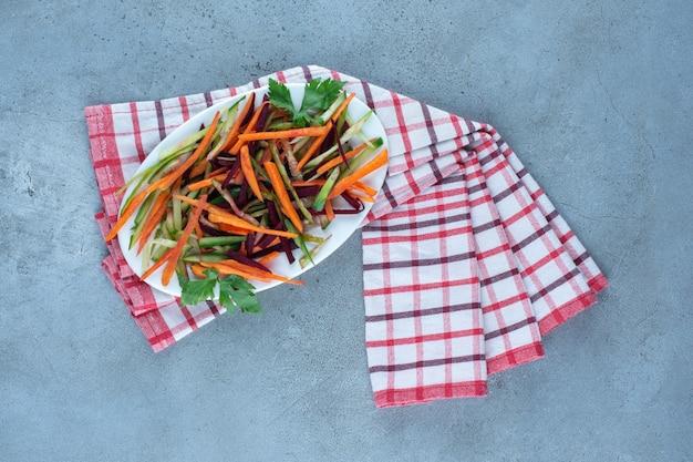Cenouras crocantes, pepinos e beterrabas picadas em uma salada de lanche em uma travessa na mesa de mármore.