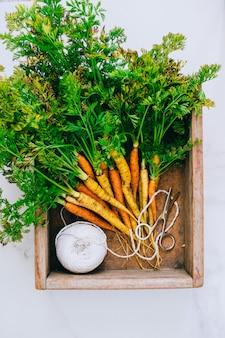Cenouras de legumes sujos frescos raízes em caixa de madeira em fundo de mármore