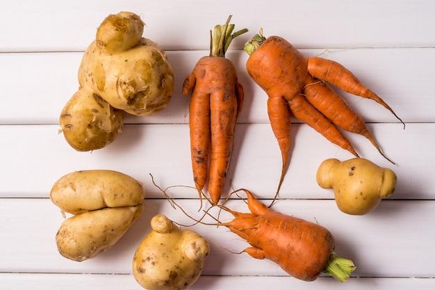 Cenouras e batata curvadas feias na moda na tabela de madeira branca.