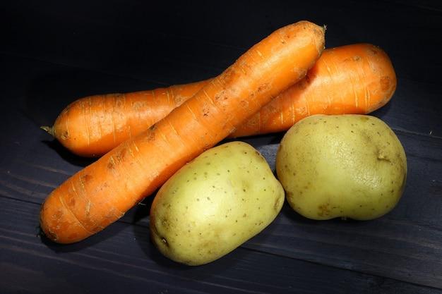 Cenouras e batatas em um fundo escuro