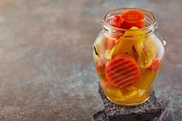 Cenouras e brócolis em conserva em uma jarra de vidro