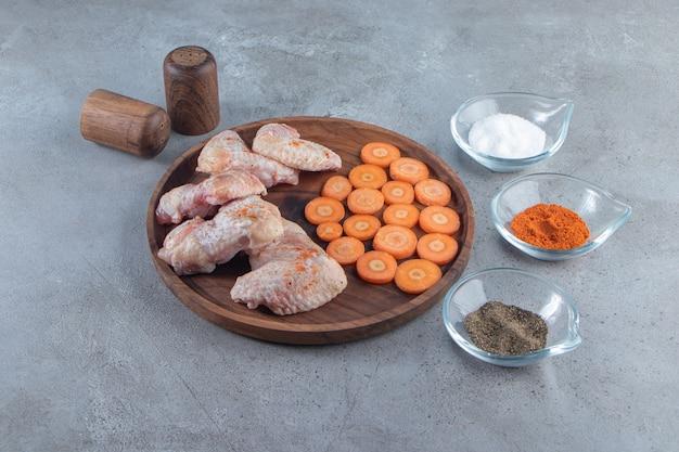 Cenouras fatiadas e asas de frango em uma placa de madeira ao lado de tigelas de temperos, na superfície de mármore.