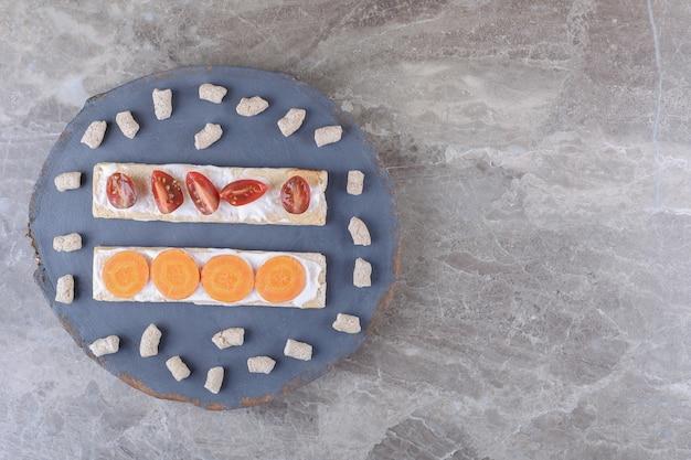 Cenouras fatiadas e tomates em pães crocantes, rodeados por migalhas no tabuleiro, na superfície de mármore