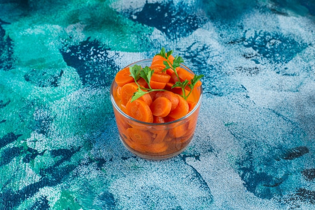 Cenouras fatiadas em um copo, no fundo azul.