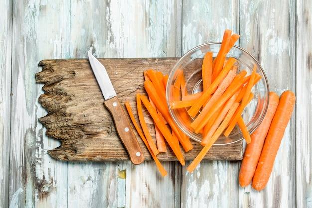 Cenouras fatiadas em uma placa de corte com uma faca. em madeira