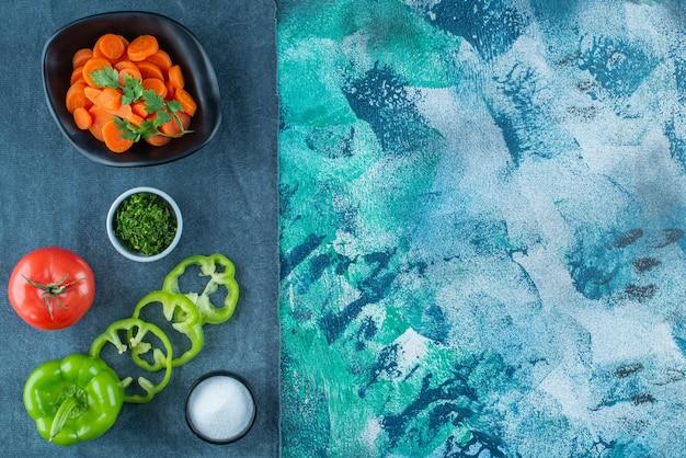 Cenouras fatiadas em uma tigela ao lado de vegetais em uma toalha, na mesa azul.