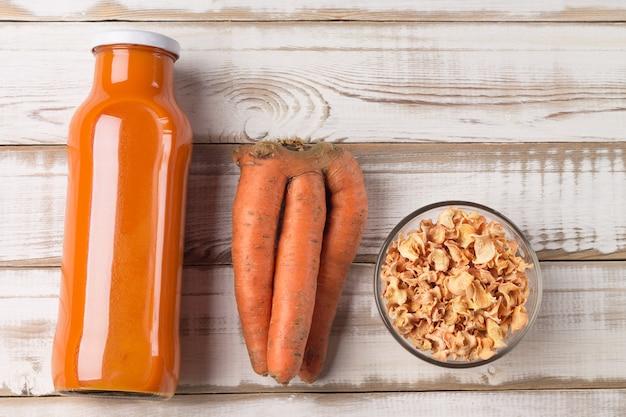 Cenouras feias, batatas fritas secas e suco de cenoura natural em uma garrafa, sobre uma mesa de madeira clara
