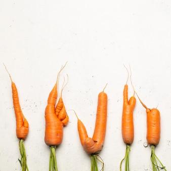 Cenouras feias em um fundo branco. conceito de comida feia, vista superior.