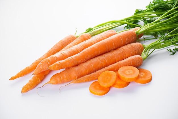 Cenouras frescas com fatias e folhas isoladas